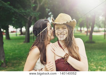 Two happy young girls gossiping and laughing. Women friendship, walk in the park outdoors. Caucasian boho girl with asian friend