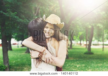 Two happy young girls hug each other. Females embracing, laughing and excited. Woman friendship, walk in the park outdoors. Caucasian boho girl with friend