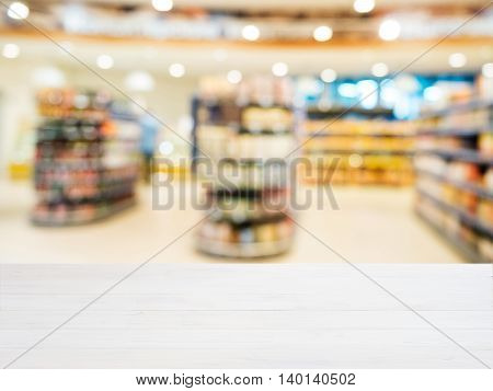 White wooden board empty table in front of blurred background. Perspective white wood over blur in supermarket - can be used for display or montage your products. Mockup for display of product.