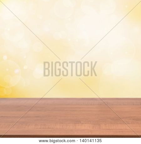 Dark wooden board empty table in abstract gold background with bokeh. Perspective brown wood board over blurred orange background - mockup for display of product