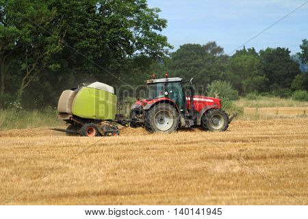 red tractor and green trailer in a field making hay bales