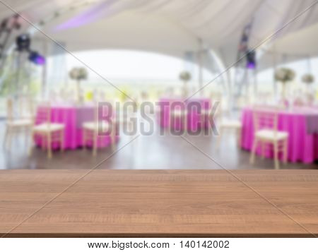 Dark wooden empty table in front of blurred restaurant interior background. Perspective brown wood board over blur in restaurant or cafe - mockup for display or montage your products