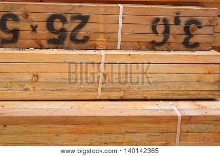 Part of a stack of orange treated cut timber beams, marked with measurements