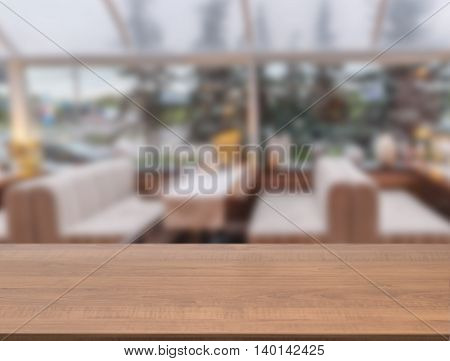 Dark wooden board empty table in front of blurred background. Perspective brown wood over blur in cafe interior - can be used for display or montage our products. Mockup your products