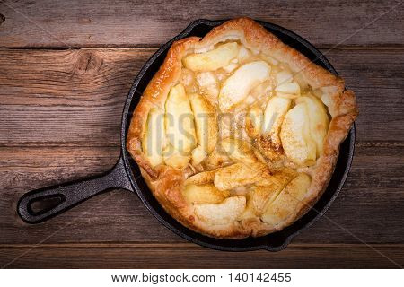 Apple Tarte Tatin, in cast iron skillet  over old wood background. Retro style processing with intentional vignette.