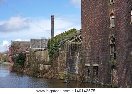 Derelict industrial warehouse and factory buildings, with broken and boarded up windows and overgrown vegetation, alongside an urban canal