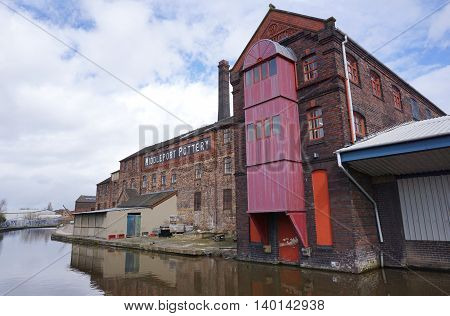 STOKE-ON-TRENT, UK - MARCH 29: A historic warehouse building sits alongside a canal in an industrial area of Stoke-on-Trent, England on March 29, 2016.