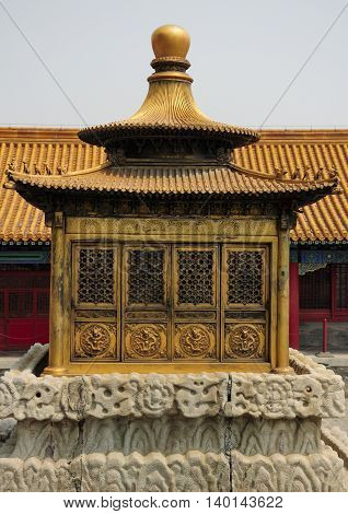 A large brass prayer shrine covered in dragons within the Forbidden City in Beijing China.