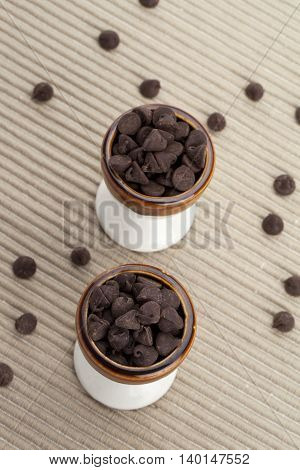 two cups of chocolate chips with strayed chips on the side