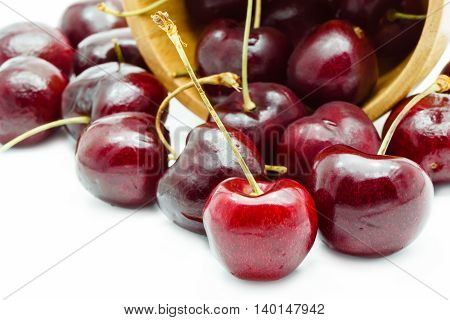 Cherries in wooden bowl on white background Delicious fruit concept