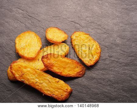 Roasted potato wedges with rosemary and thyme on a dark slate background with space for text