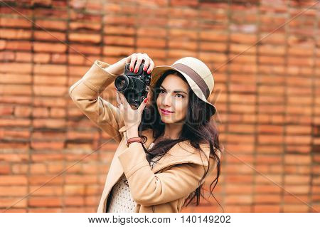 cute one girl photographer on a background of a brick wall . woman takes on a film camera on the street