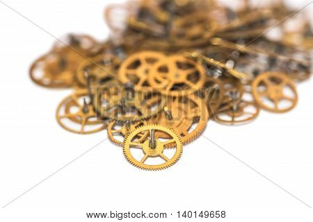 A pile of gear. Many mechanisms. Old vintage gears. Part of clockwork. The natural color and texture. Focus on front blurred background. Golden cogs.