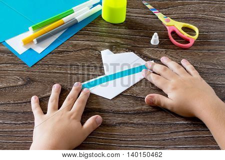 Child Glues The Paper Strip. The Child Makes Crafts Out Of Paper Boat. Glue, Paper, Scissors On A Wo