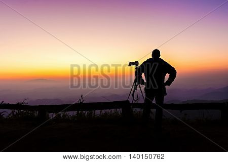 Silhouette Of Photographer Standing At View Point In Twilight