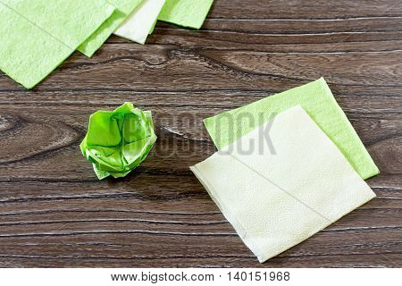 The Child Fold A Square Of Paper. The Child Makes Crafts Out Of Paper Lily. Paper Napkins On A Woode