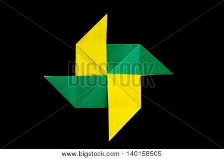 Origami paper windmill isolated against a black background