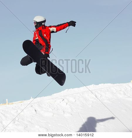 Snowboard sportsmen in jump over clear blue sky