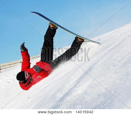 Snowboard sportsmen in fall over clear blue sky