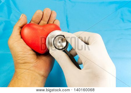 heart check up by stethoscope. red heart shape in hand on blue fabric background.
