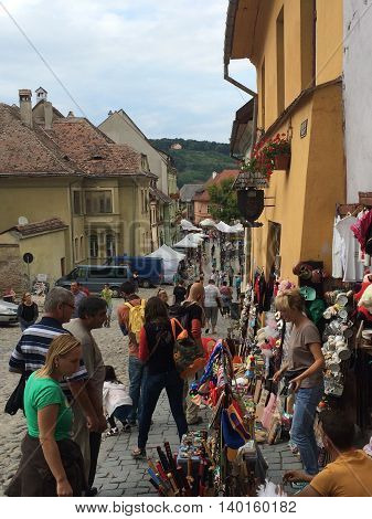 Romania, August 21, 2015, Sighisoara, Transylvania, People in an old street with small shops