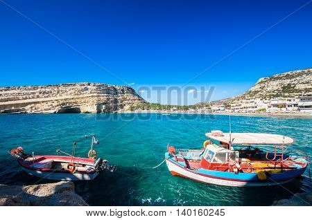 Matala beach on Crete island, Greece. There are two boats in the foreground and many caves near the beach.