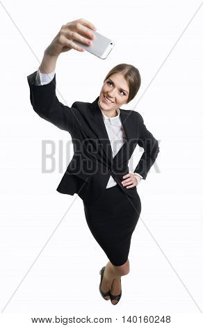 Girl in business clothes with a phone in his hand shoots himself.