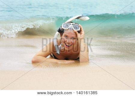 Young beautiful girl with an underwater mask lies on the beach in the sand close up. Smiling in anticipation of larger wave back.