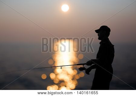 fisherman at dusk. silhouette of a fisherman with a fishing rod in the background reflected in water sunset