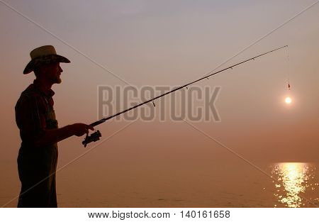 fisherman with a fishing rod on the background of sunset. dark silhouette of a fisherman with a fishing rod in the hands who is trying to catch the setting sun. the concept of aging