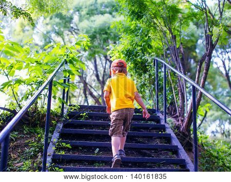 toddler climbs the stairs in the park. concept of growing up. step by step the child rises higher and goes farther