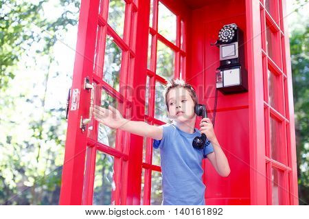 boy closes the door of the red telephone booth. boy talking on the phone in a red phone box and closes the door that opened a gust of wind. scared kid
