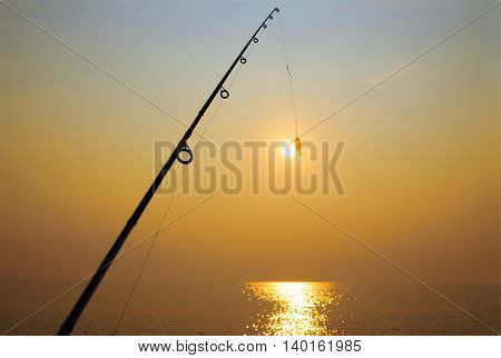 fly-fishing. fishing rod and jig on background of the setting sun. attempt to catch the setting sun fishing rod on the hook. the concept to extend the moment