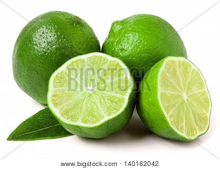 two limes with two halves and leaf isolated on white background.