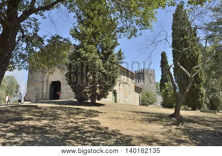 GUIMARAES, PORTUGAL - AUGUST 9, 2015: People around the Church of Saint Miguel do Castelo a romanesque church constructed and views of the Castle behind it in Guimaraes Portugal.