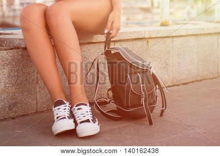 closeup of woman legs in white gumshoes, outdoor shot