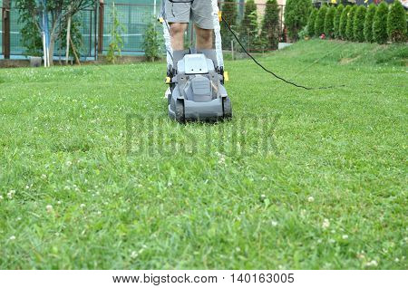 Man is pushing a mower to cut the grass in his garden