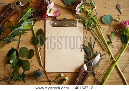 Clipboards holder on a wooden table with flowers and shears . Create bouquets.