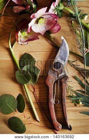 Secateurs with wooden handle with flower on wooden background.