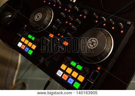 stand of deejay with colored buttons in night club