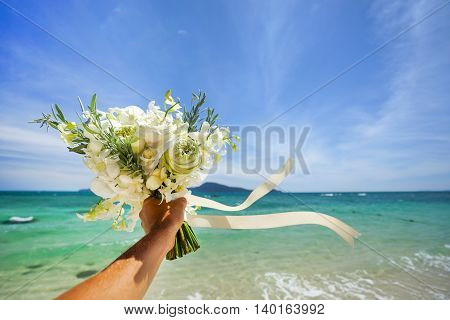 Wedding bouquet of white flowers in hand . Against the background of blue sea and tropical islands .