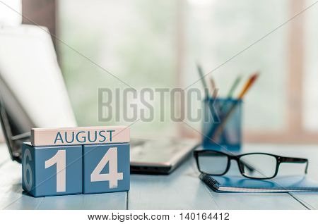 August 14th. Day 14 of month, wooden color calendar on IT-office background. Summer time. Empty space for text.