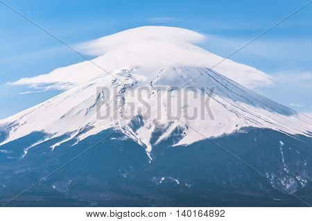 Mt.Fuji wearing hat-shape clound with blue sky in background.
