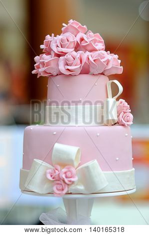 Exquisite pink wedding cake of three levels with a blurred background