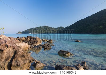 Rock on the shore and sea view with mountain and clear sky in background