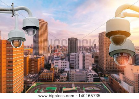 Closeup CCTV camera outdoors with colorful cityscape background.