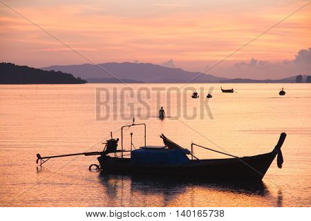 Sunset scene with orange shade of the sky with boat floating on the sea.