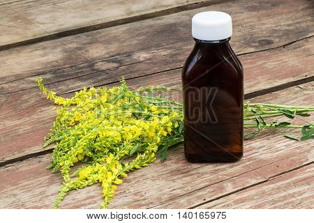 Melilotus officinalis known as yellow sweet clover yellow melilot ribbed melilot common melilot and pharmaceutical bottle on old wooden table. Used in herbal medicine as well as pasture or livestock feed is a major source of nectar