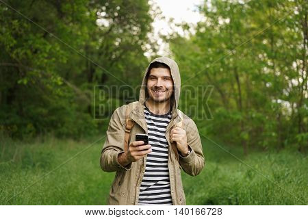 Portrait of a smiling young man with a pilgrim backpack walking along the road happy camper walking alone on a summer day the traveler enjoying their time enjoying the outdoors.