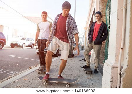 Positive teenage friends with skateboards walking down the street in summer day